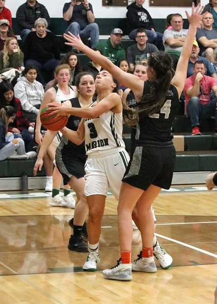 PMG PHOTO: PHIL HAWKINS - North Marions Mya Hammack goes around Gladstones Jade Rowley (24) and scores to give the Huskies a 44-42 lead with 3:28 remaining Friday.
