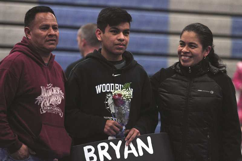 PMG PHOTO: PHIL HAWKINS - Senior Bryan Ramirez stands between his parents as head coach Dusty Price recognizes him during Woodburns mid-match interlude.