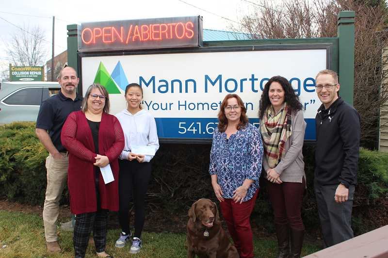 DESRIEE BERGSTROM/MADRAS PIONEER - Mann Mortgage presented two checks, one to Madras high School Key Club and another to Operation Rudolph as a part of its Your Vote Matters program.