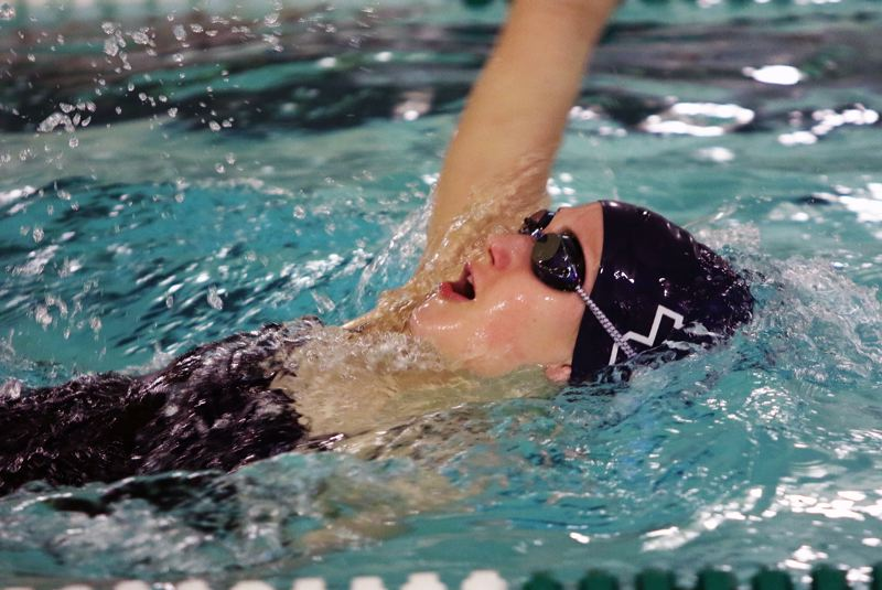PMG PHOTO: DAN BROOD - Lake Oswego sophomore Olivia Anderson swims to victory in the 100-yard backstroke during her team's 89-78 loss to Tigard at Tigard Aquatic Center on Thursday, Jan. 30.