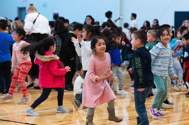 PMG PHOTO: CHRISTOPHER OERTELL - Students dance La Raspa in the first-ever activity at Eastwood Elementary School's new gym on Tuesday, Feb. 4.