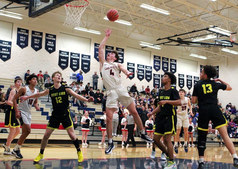 PMG PHOTO: MILES VANCE - Lake Oswego senior guard Jack Chlumak floats in a short shot during his team's 58-47 overtime win over West Linn at Lake Oswego High School on Wednesday, Feb. 5.