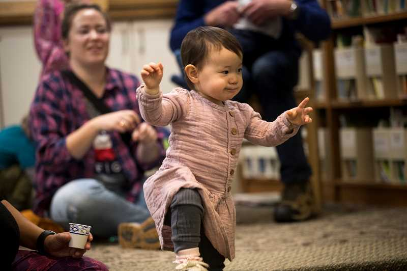 PMG PHOTO: JAIME VALDEZ - Nora Crop, 2, mimics hand motions from Michaela Weilert who was reading a book in sign language during a Multicultural Children's Book Day event at Lake Oswego Library.