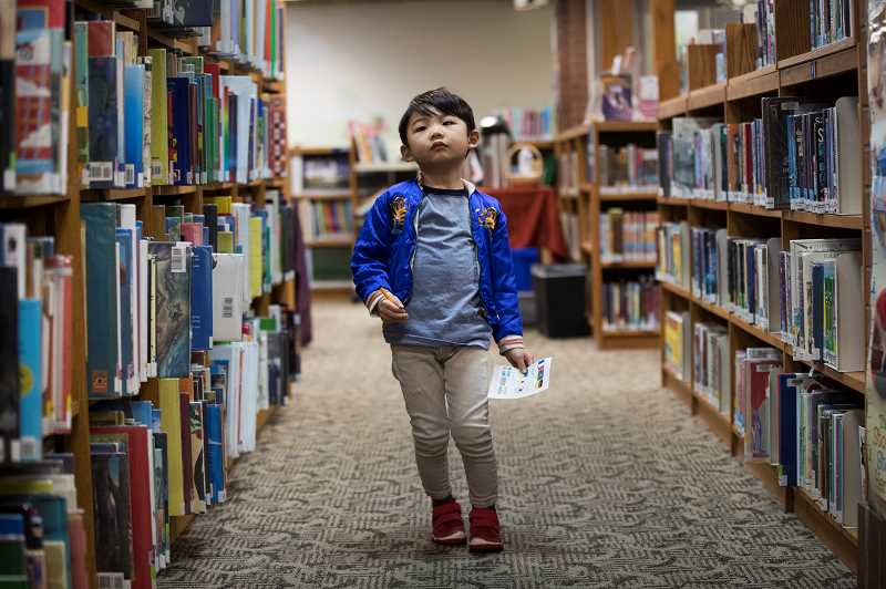PMG PHOTO: JAIME VALDEZ - Atticus Buenjemia, 4, looks for international flags in a scavenger hunt throughout Lake Oswego Library during a Multicultural Children's Book Day event at the library.