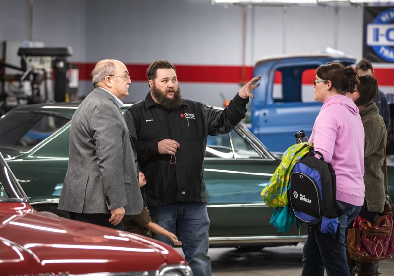 PMG PHOTO: JONATHAN HOUSE - Clackamas Community College  automotive department instructor Mark House chats with attendees during the Automotive Expansion Grand Opening.
