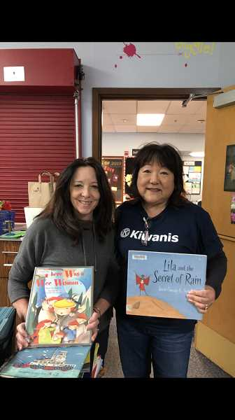 COURTESY PHOTO: JOYCE HANDA - Joyce Handa at River Grove Elementary School in Lake Oswego donating gently used books to Ana Ryan, secretary to the principal on behalf of SW Hills Kiwanis.