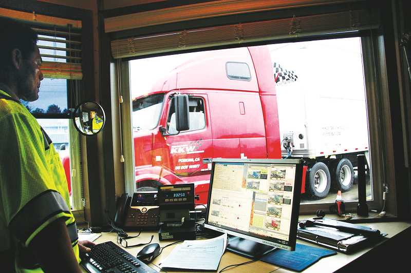 PMG PHOTO - Weighmaster Tom Avila weighs a Freightliner tractor-trailer as it moves across the scales located at the Woodburn port of entry.