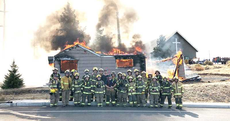 SUBMITTED PHOTO - More than two dozen volunteers, along with two staff firefighters for the Jefferson County Fire District, pose beside a house being used as a 'burn to learn' building in 2018. The house was owned by Madras United Methodist Church.