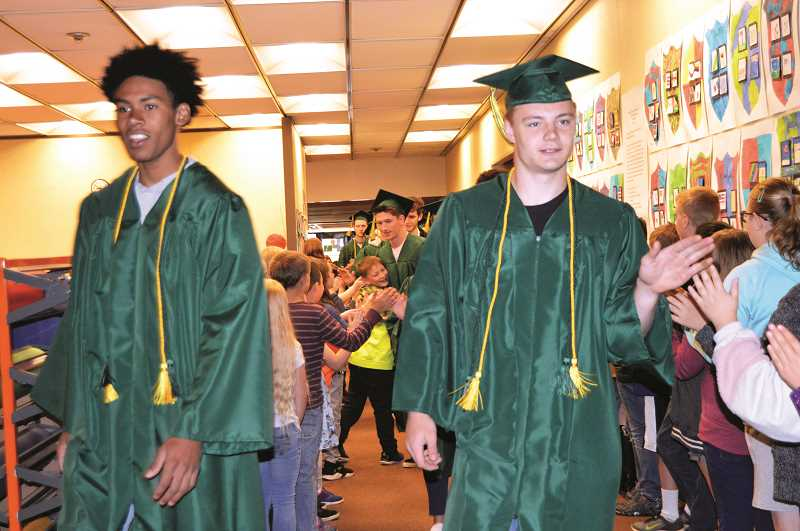 PMG FILE PHOTO: CINDY FAMA - Colton 2019 graduates Javontae Maes and James Parker give out high fives on the last day of school during the senior parade through district schools.
