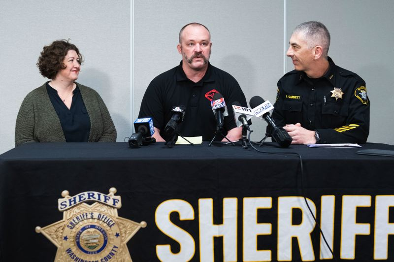 PMG PHOTO: CHRISTOPHER OERTELL - Washington County Cpl. Jeremy Braun, center, with his wife, Joy, and Sheriff Pat Garrett speaking about an August shootout near Henry Hagg Lake that left Braun severely wounded.