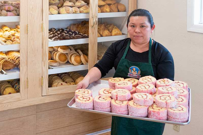 COURTESY PHOTO: CHRISTOPHER OERTELL - Owner Lucia Trinidad-Cauich holds a tray of Niño Envuelto which is similar to a jelly roll at the La Panadera bakery in Forest Grove. The bakery opened last November.