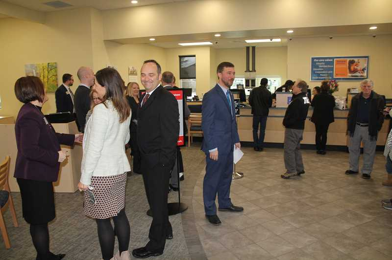 PMG PHOTO: JUSTIN MUCH - Branch Manager Patrick Schmerber, center, greets visitors as a couple dozen celebrants turn out for a ribbon cutting to celebrate Woodburns Oregon State Credit Unions move into its new building, located between Wheeler Dealer and Coastal Farm & Ranch, On Friday, Feb. 7.