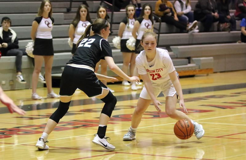 PMG PHOTO: JIM BESEDA - Oregon Citys Mia Martineau (23) looks for room to manuever around Tigards Delaney Leavitt (22) in the second half of Wednesdays home game.