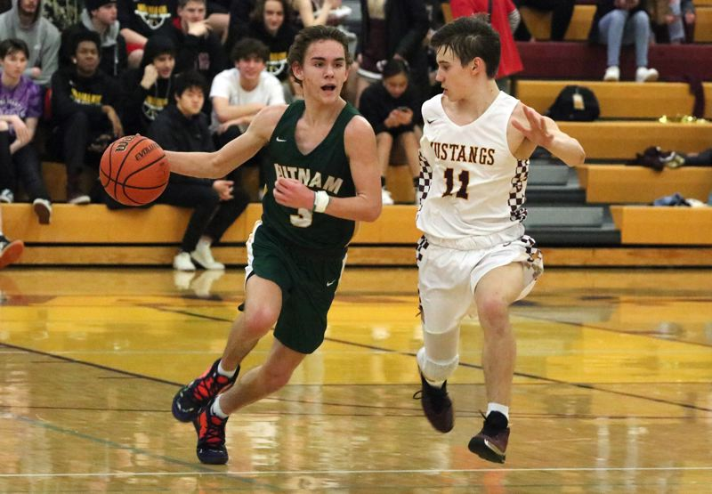 PMG PHOTO: JIM BESEDA - Putnam's Grant Ferguson pushes the ball up the court under pressure from Milwaukie's Deegan McCord (11) in the second half of Friday's Northwest Oregon Conference boys basketball game.