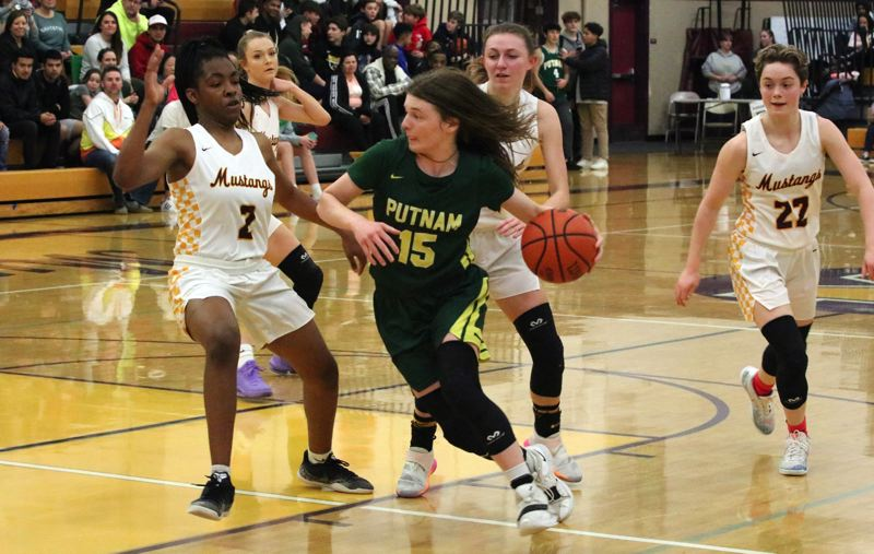 PMG PHOTO: JIM BESEDA - Putnam's Maddie Olma drives against Milwaukie's Aubrey Miller during the first half of Friday's Northwest Oregon Conference girls basketball game at Milwaukie High School.