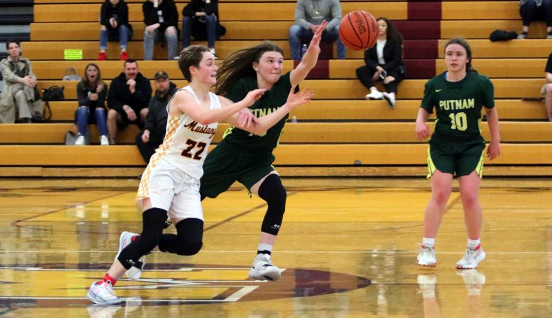 PMG PHOTO; JIM BESDEA - Milwaukie's Cali Denson (left) and Rex Putnam's Madelyn Olma fight for possession of the ball during the Mustangs' 63-60 win at Milwaukie High School on Friday, Feb. 7.