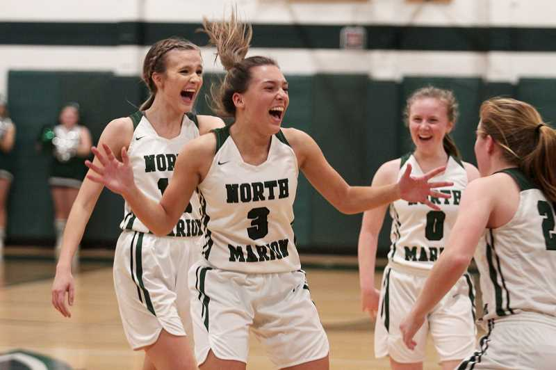 PMG PHOTO: PHIL HAWKINS - North Marion junior Mya Hammack celebrates with her teammates after sinking a 75-foot shot from near the Husky bench at the end of the second quarter against Molalla. Hammack finished with a game-high 21 points to lead the Huskies to a 60-31 win over the Indians.