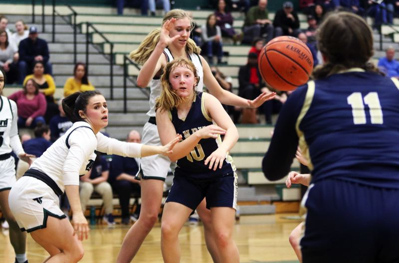 PMG PHOTO: DAN BROOD - Canby freshman guard Allie Mead (10), guarded by Tigard senior Kennedy Brown (left) and Sarah Lamet, fires a pass to Cougar senior Arika Evans during Friday's Three Rivers League game.