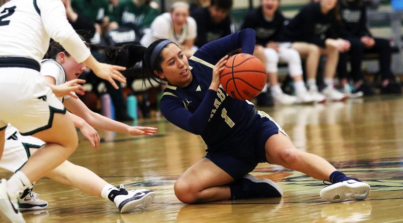 PMG PHOTO: DAN BROOD - Canby High Schoo senior Naarai Gomez grabs a loose ball and looks to make a pass during the Cougars' 51-40 win at Tigard in Friday's Three Rivers League game.
