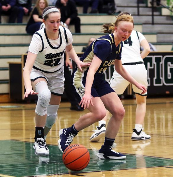 PMG PHOTO: DAN BROOD - Tigard senior Delaney Leavitt (left) and Canby junior Zoe Thompson go for a loose ball during Friday's Three Rivers League game.