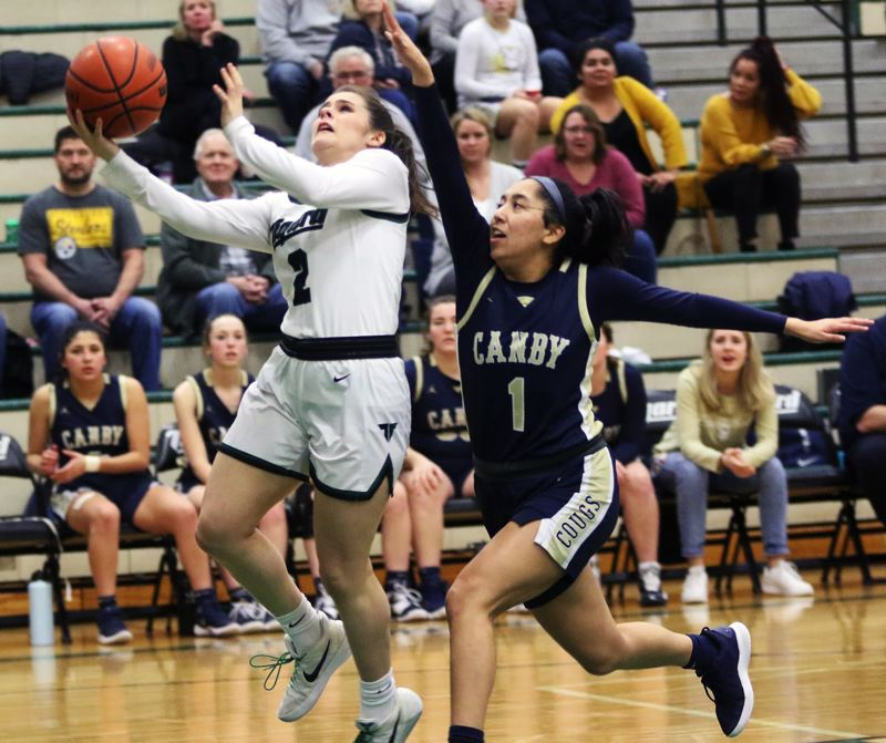 PMG PHOTO: DAN BROOD - Tigard High School senior Kennedy Brown (left) looks to go up to the basket against Canby senior Naarai Gomez during Friday's Three Rivers League contest.
