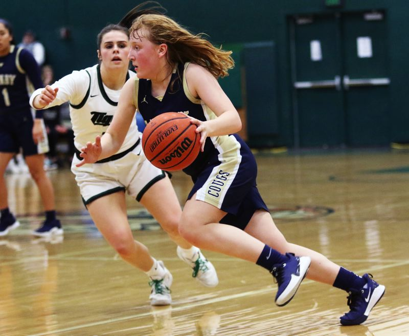 PMG PHOTO: DAN BROOD - Canby High School freshman guard Allie Mead looks to drive to the basket during the Cougars' 51-40 win at Tigard in Friday's Three Rivers League game.