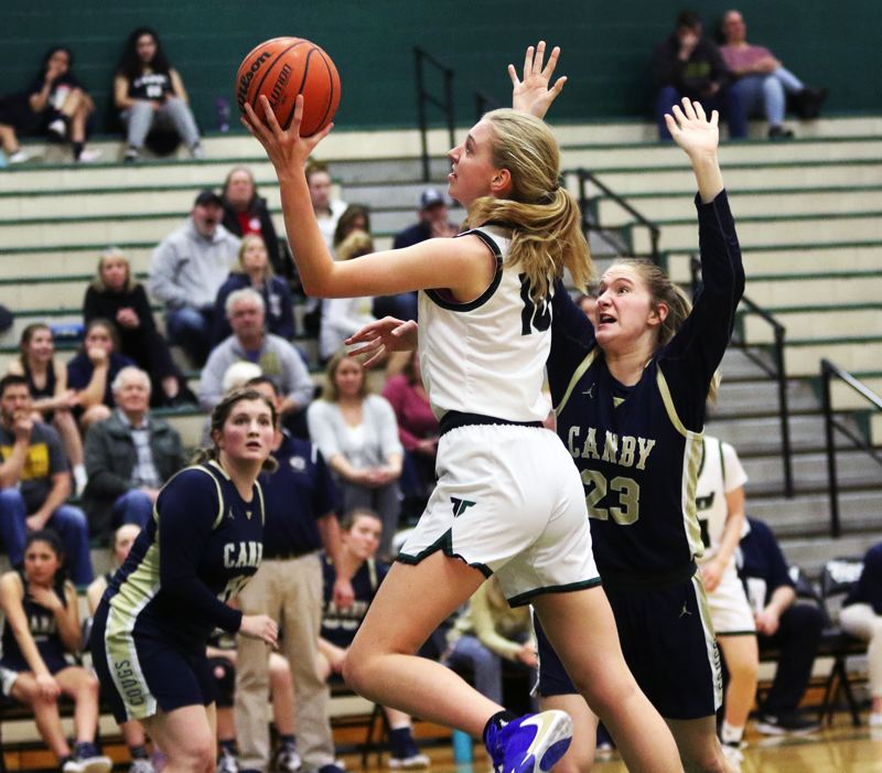 PMG PHOTO: DAN BROOD - Tigard High School sophomore post Sarah Lamet goes to the basket against Canby senior Nicole Mickelson during Friday's Three Rivers League contest.
