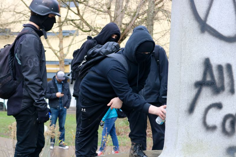 PMG PHOTO: ZANE SPARLING - Several people wearing black-bloc style antifacist outfits watch as a person spraypaints the Soldiers Momument in Lownsdale Square in Portland during a protest on Saturday, Feb. 8.