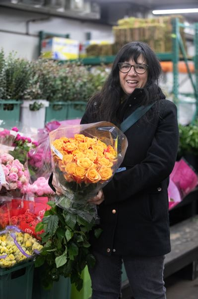 PMG PHOTO: JONATHAN HOUSE - Florist Staci Gundry, owner of Bodle Frog Botanical, checks out the roses at the Portland Flower Market on Swan Island. At this industry-only wholesale market, stems cost about one third of their final retail cost.