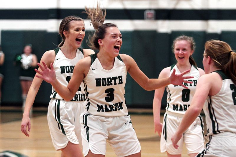 PMG PHOTO: PHIL HAWKINS - North Marion junior guard Maya Hammack (no. 3) and her teammates celebrate after she sank a three-quarters court shot to beat the halftime buzzer in her team's 60-31 win over Molalla on Friday, Feb. 7.