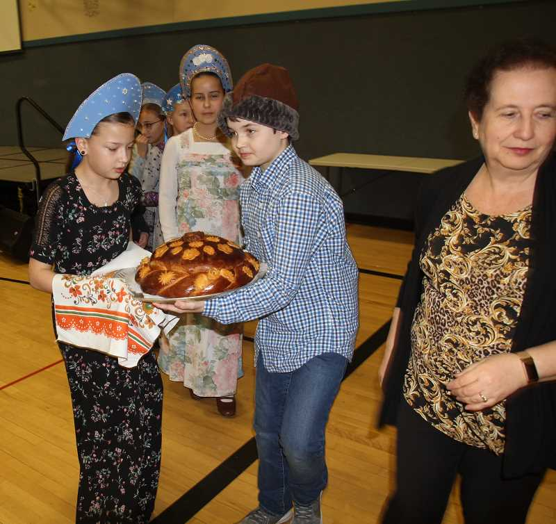 PMG PHOTO: JUSTIN MUCH - Heritage Elementary math coach Liliya Zaltzman, right, watches the Russian Winter Festival activities while fourth graders Sofia Cam and Alexander Huelsman carry the karavai as Katya Afanasiev, Faina Kalugin and Kalyssa Reutov follow.