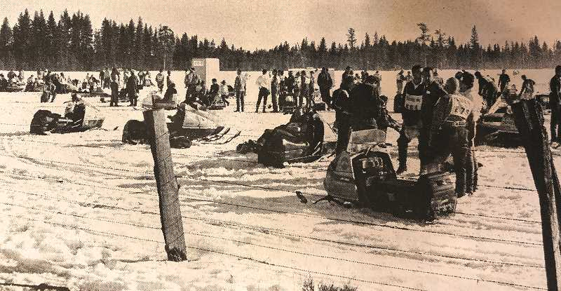 CENTRAL OREGONIAN - FEB. 12, 1970: On the Line - Snowmobilers wait for their chance at the starting line during Sunday's competition in the snowmobile races sponsored at Big Summit Prairie. Contestants chatted casually, compared machines, and some even stretched out on their snowmobiles for a catnap while other entries competed in their divisions. Many of the entries said that the two-day affair, sponsored by the local Hi-Lo-Sno-Go snowmobile club, was one of the best that they have attended.