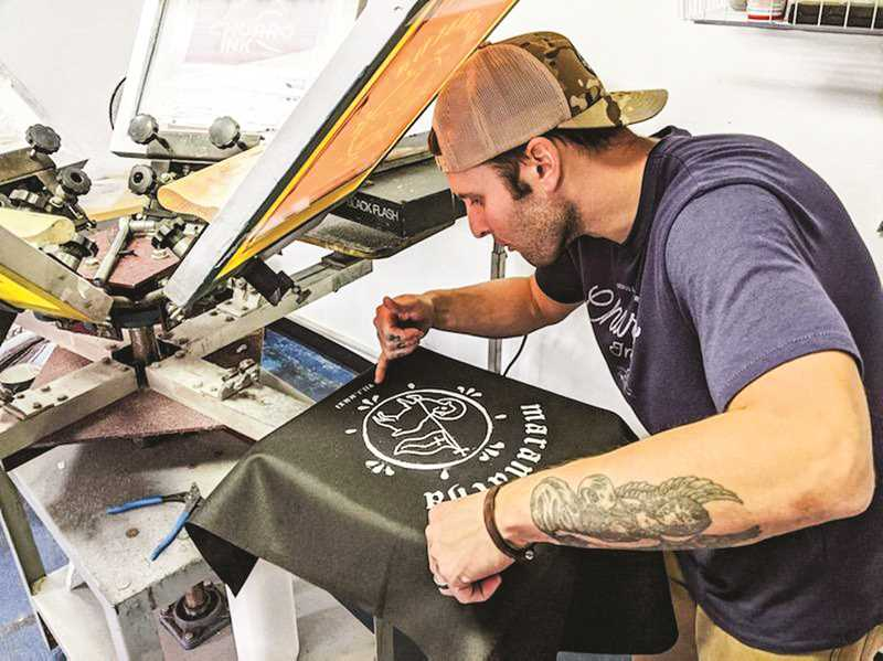 PHOTO COURTESY OF TAYLOR HANSEN - Alex Bava operating his screenprinting equipment, as he works on a design for a shirt.