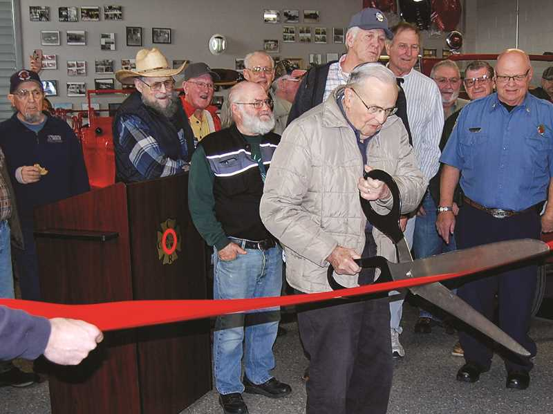 RAMONA MCCALLISTER - Sid Harper, the oldest living CCFR volunteer, cuts the ribbon at the fire museum dedication last month.