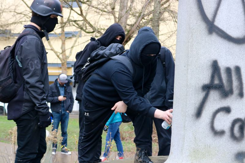 PMG PHOTO: ZANE SPARLING - Several people wearing black-bloc style anti-facist outfits watch as a person spraypaints the Soldiers Momument in Lownsdale Square in Portland during a protest on Saturday, Feb. 8.