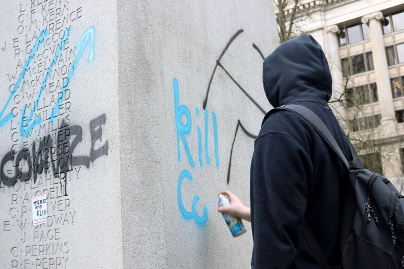 PMG PHOTO: ZANE SPARLING - A person dressed in black spraypaints graffiti on the Soldiers Monument in Lownsdale Square in downtown Portland on Saturday, Feb. 8.