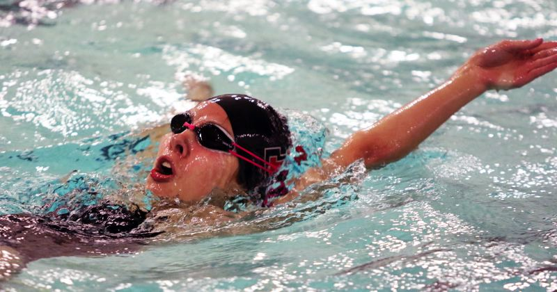 PMG PHOTO: DAN BROOD - Tualatin High School junior Izzy Ehmig picks up a victory in the 100-yard backstroke event during the Timberwolves' Three Rivers League win over rival Tigard.