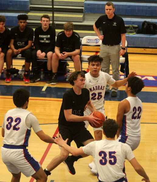 PMG PHOTO: STEELE HAUGEN - Estacadas Nate Hagel is surrounded by a herd of White Buffalo defenders on a drive in the second half, while Rangers head coach Kyle Gilstad looks on from the bench.