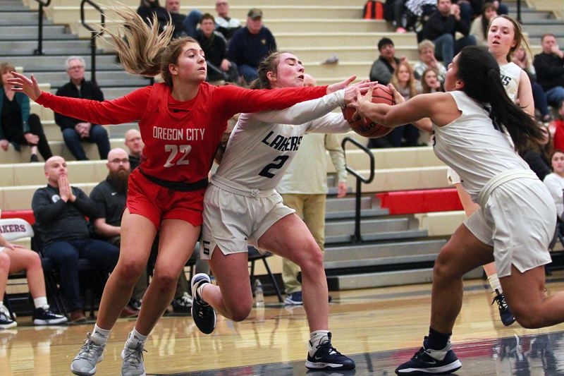 PMG PHOTO: MILES VANCE - Lake Oswego's Emma Jeanson (center) and Lauren Smith battle Oregon City's Katie Kathan for possession of the ball during the Lakers' 38-20 loss to the Pioneers at Lake Oswego High School on Tuesday, Feb. 11.