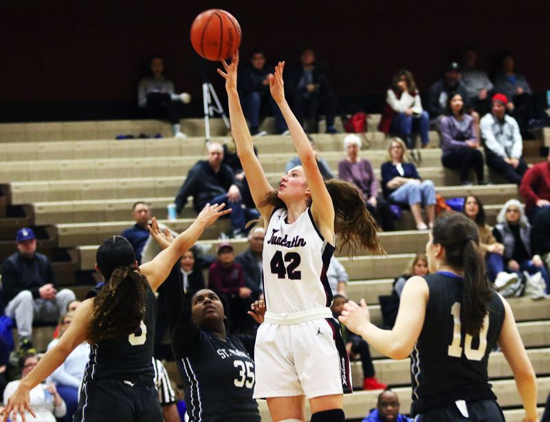 PMG PHOTO: DAN BROOD - Tualatin High School junior post Natalie Lathrop (42) goes up high to shoot for two of her career-high 35 points in the Timberwolves' 66-40 win over St. Mary's on Tuesday.