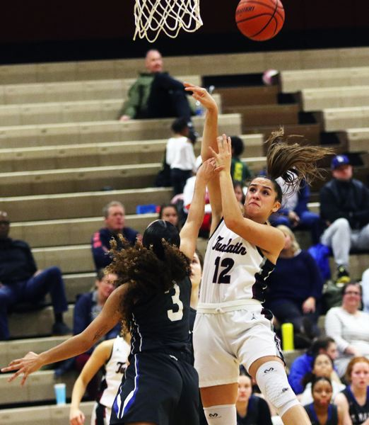 PMG PHOTO: DAN BROOD - Tualatin High School junior Sidney Dering (12) is fouled by St. Mary's senior Marley Johnson as she puts up a shot during the Wolves' 66-40 win on Tuesday.