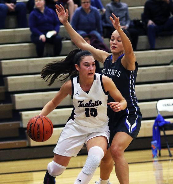 PMG PHOTO: DAN BROOD - Tualatin High School junior Aurora Davis (left) drives the baseline against St. Mary's senior Marley Johnson during Tuesday's game. The Wolves won 66-40.