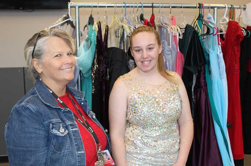 TONY AHERN/MADRAS PIONEER - Juanita Payton, left, and Madras High School senior Katie Weygandt  with the prom dresses Payton has collected to share with students.