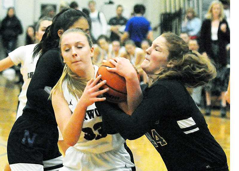 GRAPHIC PHOTO: GARY ALLEN - NHS junior Paige Krebs (right) fights for the ball in the Tigers' 41-38 loss to Sherwood on Friday evening.