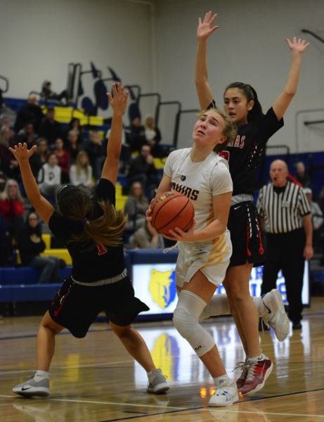 PMG PHOTO: DAVID BALL - Barlows Kennedie Shuler squeezes through a pair of defenders to get to the basket during the Bruins 53-50 loss to Clackamas on Tuesday night.