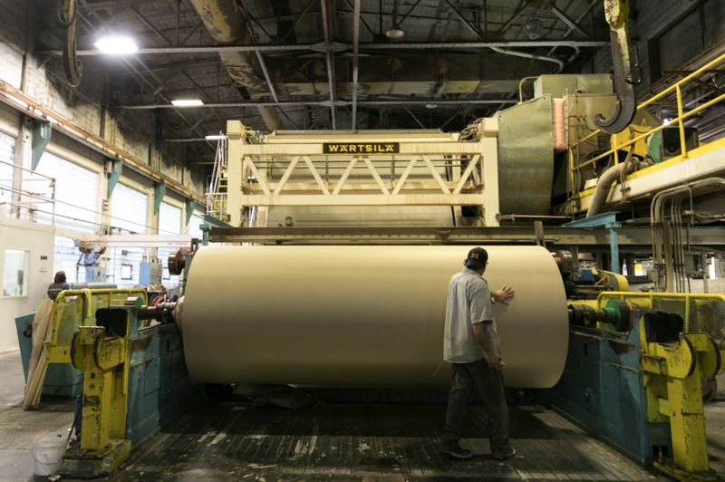 PAMPLIN MEDIA GROUP: JAIME VALDEZ - A worker at the Willamette Falls Paper Company in West Linn feels a spinning roll of craft paper, made with 40 percent straw fiber, to check it for inconsistencies.