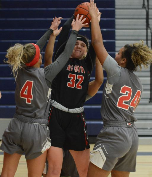 PMG PHOTO: DAVID BALL - Mt. Hood center Emily Webber pulls down a rebound out of a crowd of Clackamas players to give the Saints possession for its winning bucket.