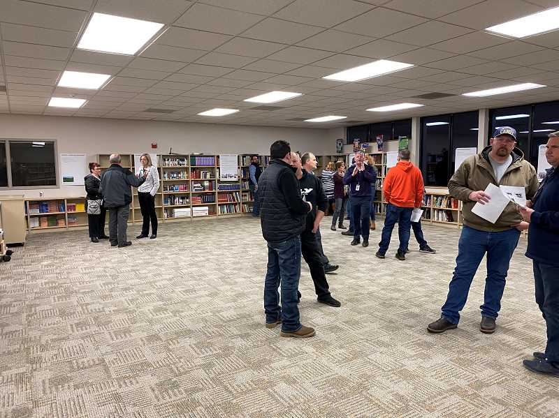 PMG PHOTO: KRISTEN WOHLERS - Following a presentation, community members browsed the potential bond projects displayed on posters throughout Ackerman Center's library.