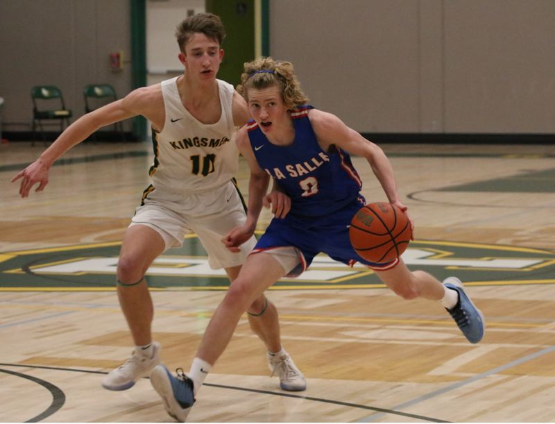 PMG PHOTO: JIM BESEDA - La Salle Prep's Ian Simmons puts a move on Putnam's Sam Sholty during the second half of Wednesday's Northwest Oregon Conference boys basketball game at Putnam High School.