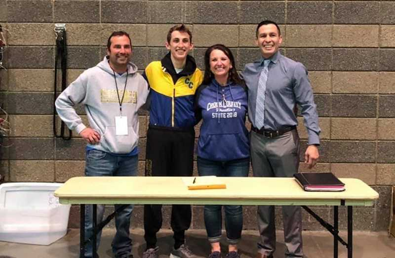 LON AUSTIN/CENTRAL OREGONIAN - Zach Mauras stands with his parents and with Eastern Oregon University head wrestling coach Dustyn Azure (far right) after signing his letter of intent to wrestle for the Mountaineers.